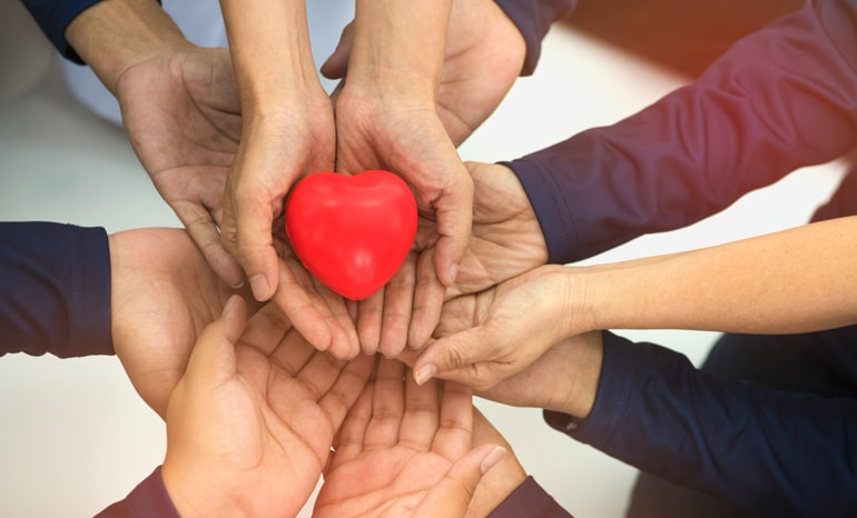 multiple hands holding a heart