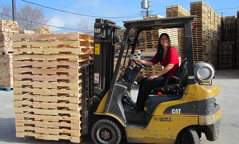 woman operating fork lift with pallets